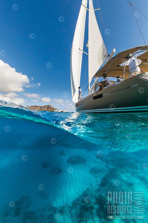 Sailboat cruising off of Waikiki and Diamond Head, O'ahu.