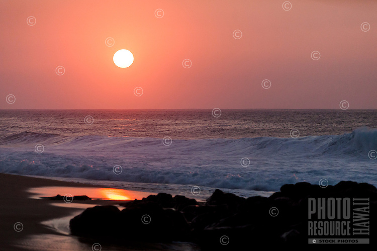 The reflection of an orange sunset nears rocks on the shore at Rock Piles Beach on the North Shore, O'ahu