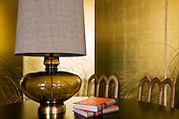 In the dining room the gold lustre of a painted screen is reflected in the glass base of a table lamp