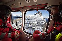 "Switzerland. Canton Ticino.A Rega Agusta AW109 SP Grand ""Da Vinci"" helicopter on a rescue mission flies above the Alps. All Rega helicopters carry a crew of three: a pilot, an emergency physician, and a paramedic who is also trained to assist the pilot for radio communication, navigation, terrain/object avoidance, and winch operations. The paramedic Giovanni Beldi (L) and the emergency physician Doctor Alessandro Genini (R) are seated in the cabin and look at the panorama. The name Rega was created by combining letters from the name ""Swiss Air Rescue Guard"" as it was written in German (Schweizerische Rettungsflugwacht), French (Garde Aérienne Suisse de Sauvetage), and Italian (Guardia Aerea Svizzera di Soccorso). Rega is a private, non-profit air rescue service that provides emergency medical assistance in Switzerland. Rega mainly assists with mountain rescues, though it will also operate in other terrains when needed, most notably during life-threatening emergencies. As a non-profit foundation, Rega does not receive financial assistance from any government. The AgustaWestland AW109 is a lightweight, twin-engine, helicopter built by the Italian manufacturer Leonardo S.p.A. (formerly AgustaWestland, Leonardo-Finmeccanica and Finmeccanica). Leonardo S.p.A is an Italian global high-tech company and one of the key players in aerospace. In close collaboration with the manufacturer, the Da Vinci has been specially designed to cater for Rega's particular requirements as regards carrying out operations in the mountains. It optimally fulfills the high demands made of it in terms of flying characteristics, emergency medical equipment and maintenance. Safety, performance and space have been increased, and maintenance and noise emissions reduced. 20.09.2017 © 2017 Didier Ruef"