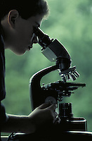 Microscope in use by a young man. Cleveland Ohio USA Cleveland Heights.