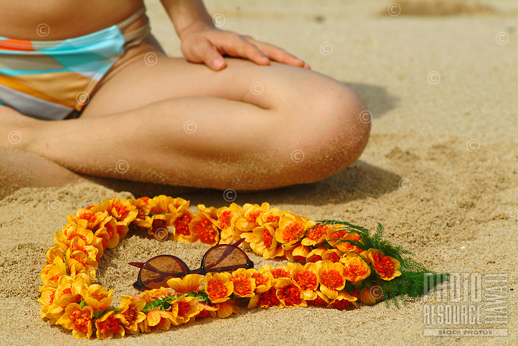 Closeup of woman sitting on beach with Ilima lei & sunglasses
