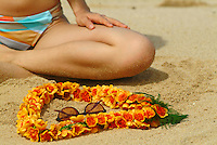 Closeup of woman sitting on beach with Ilima lei & sunglasses