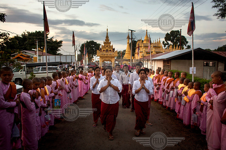 Followers of U Wirathu, the spiritual leader of the radical Buddhist 969 movement, follow his convoy into Thein Taung Monastery before he delivers a sermon in Taunggyi, Shan State. /Felix Features