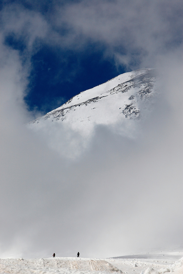 Russia, Caucasus. Skiers under Mount Elbrus, 5642 m asl, Europes highest mountain. Surronded by clouds.
