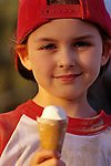 Young girl (7 years old), Little League Baseball player, eating ice cream after game, sunset light, portrait, Woodinville, Washington USA  MR.
