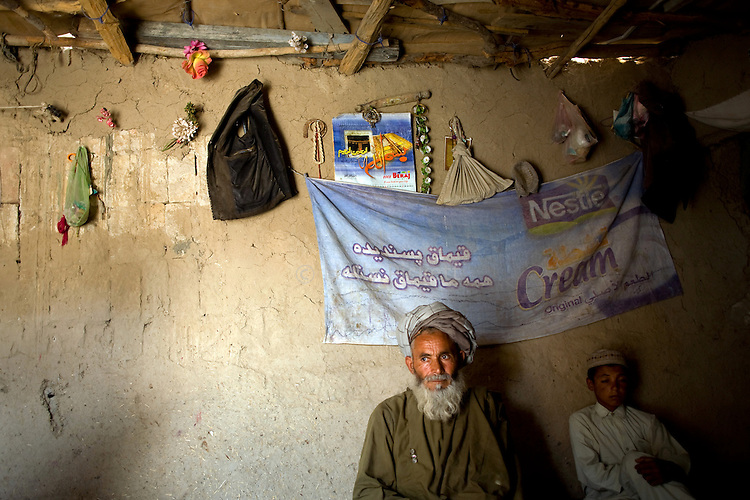 """Khalik Daad, 60, sits with his son Wali, 14, in their small mud hut near the home of Kandahar Provincial Council Chairman Ahmed Wali Karzai, who is also the brother of President Hamid Karzai, in Kandahar, Afghanistan, Aug. 21, 2009. Daad's 10-year-old daughter Jamila was killed instantly yesterday when a rocket hit the building next door and shrapnel fell into the hut where the family was preparing lunch. Daad's wife and another young daughter were also injured and taken to the hospital. """"This is not the work of Muslims,"""" Daad said. Two people died and three more were injured in Kandahar as the city was bombared by rockets throughout Afghanistan's presidential election day."""