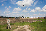 National Guard soldiers and private contractors prepare bags filled with dirt to be slung by helicopter to gaps between the barrier islands separating the Louisiana coast from the Gulf of Mexico.  The bags will be used as part of a plan to bridge these gaps in order to prevent oil from the Deepwater Horizon Oil Spill from penetrating deep into the state's fragile and pourous wetland coastal area...Deepwater Horizon Oil Spill.  The spill is estimated to be gushing 35,000 to 60,000 barells of oil into the ocean per day.  Difficulties installing monitoring devices at the source have made this number difficult to clearly ascertain.  The spill is among the world's worst.