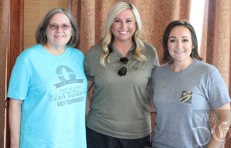 NWA Democrat-Gazette/CARIN SCHOPPMEYER Mary Canode (from left), Emily Boyd and Andrea Kennedy greet golfers at the Ozark Guidance Foundation tournament June 25.