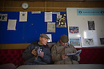 Two elderly male supporters reading their programmes in the tea room inside the ground before the Boxing Day derby match between Runcorn Town and visitors Runcorn Linnets at the Pavilions, Runcorn, in a top-of the table North West Counties League premier division match. Runcorn Linnets won 1-0 and overtook their neighbours at the top of the league in a game watched by 803 spectators. Runcorn Linnets were a successor club to Runcorn FC, one of England foremost non-League clubs of the 1970s and 1980s.