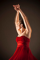 Young woman wearing red dress with arms raised