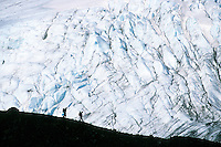 Hikers carrying backpacks descend a ridge in the Chugach Mountains, past Raven Glacier, on the Cross Pass Trail. The route runs through the Chugach National Forest from Girdwood to Eagle River, Alaska, near Anchorage.