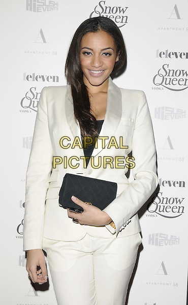 Amal Fashanu.The Snow Queen Vodka calendar launch party, Gallery Different, Percy St., London, England..December 18th, 2012.half length black  black jacket white trousers suit clutch bag .CAP/CAN.©Can Nguyen/Capital Pictures.