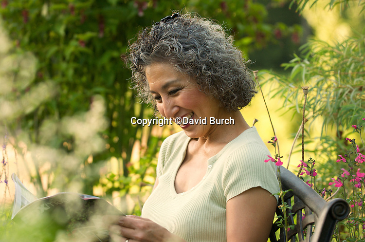 Asian woman reading a magazine and smiling in her garden