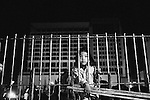 CAMBODIA  -  APRIL 18, 2005:   A young girl wathces a carnival through a fence at night in Phnom Penh on April 18, 2005 in Cambodia.  (PHOTOGRAPH BY MICHAEL NAGLE)