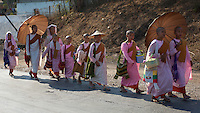 A crocodile of young Buddhist nuns tramps wearily along the road outside Hsipaw in Myanmar with only a few parasols to shade them from the fierce daytime sun.