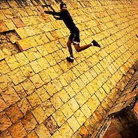 A Colombian parkour runner jumps on the wall during a free running training session held in a park in Kennedy, Bogotá, Colombia, 20 February 2016.