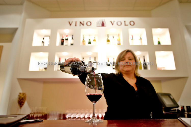3/24/2008--Seattle, WA, USA..Kyla Landy pours wine for customers at Vino Volo's wine tasting room at Seatac Airport in Seattle, Wash. Vino Volo is changing the way people travel by offering a sophisticated respite where travelers can taste great wines, enjoy small plates, and unwind in plush leather lounge chairs right next to their boarding gates. Every wine selection is available by the taste, by the glass, by the bottle, or in a tasting flight, with prices ranging from $6 to $14 per glass.Vino Volo currently operates in Washington DC?s Dulles International Airport?s (IAD) Concourse C, Seattle-Tacoma International Airport?s (SEA) Central Terminal Marketplace, Sacramento International Airport?s (SMF) Terminal A, Baltimore/Washington International Thurgood Marshall Airport?s (BWI) Terminal A, and New York?s JFK International Airport?s (JFK) Terminal 8...©2008 Stuart Isett. All rights reserved.