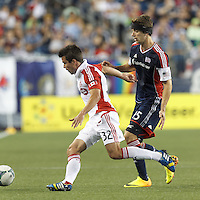 Toronto FC forward Andrew Wiedeman (32) attempts to control the ball as New England Revolution defender Stephen McCarthy (15) pressures. In a Major League Soccer (MLS) match, Toronto FC (white/red) defeated the New England Revolution (blue), 1-0, at Gillette Stadium on August 4, 2013.