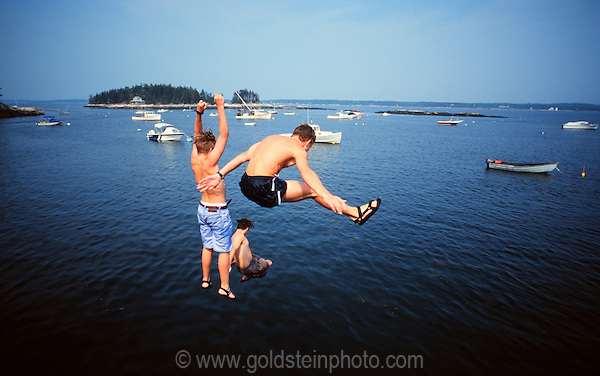 3 boys jumping from a dock into the water. Somewhere on the coast of Maine