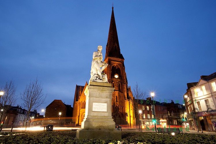 The poet Robert Burns statue in Dumfries town centre with Greyfriars Church behind at night Scotland UK