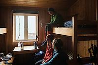 Group of hikers relax in room at Tjäktja hut, Kungsleden trail, Lapland, Sweden