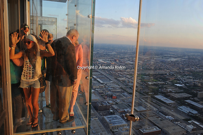 "(Left) Carolina Manrique, 15, of Colombia puts her hands on the glass of the newly opened glass balconies ""The Ledge"" at the Skydeck at the Sears Tower in Chicago, Illinois on July 6, 2009."