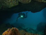 Kenting, Taiwan -- Diver with a torch exploring an underwater cavern.