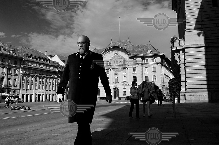 A hussier for the Federal Council walks on Bundesplatz (Parliament Square). Behind him is the Swiss National Bank building and the the Parliament just visible on the right. /Felix Features