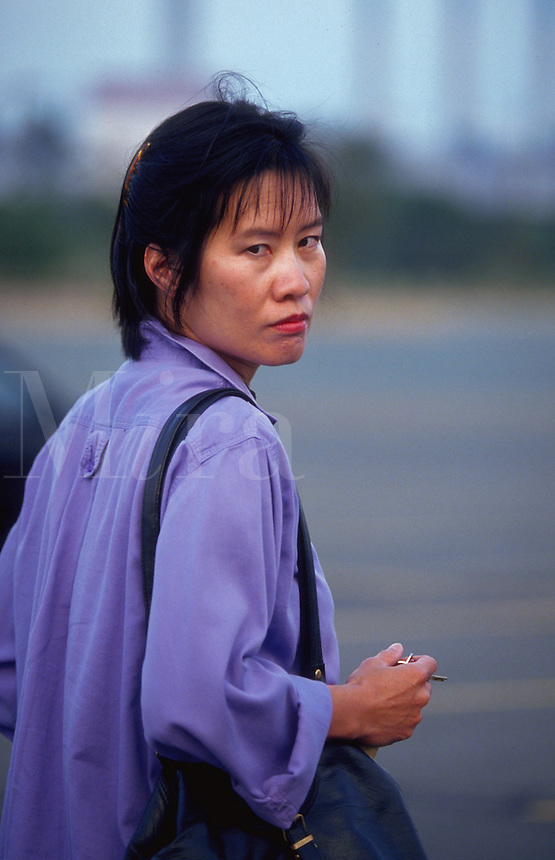 Asian-American woman looking over her shoulder with distrust, holding her keys tightly in her hand.