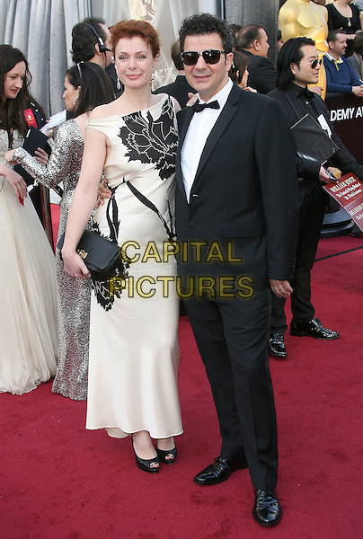 guest & Ludovic Bource.84th Annual Academy Awards held at the Hollywood & Highland Center, Hollywood, California, USA..February 26th, 2012.oscars full length white dress black tuxedo sunglasses shades .CAP/ADM.©AdMedia/Capital Pictures.