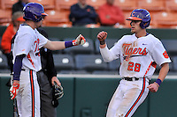 Right fielder Seth Beer (28) of the Clemson University Tigers, right, is congratulated by Adam Renwick (11) after scoring a run in the fourth inning of a game against the Wofford College Terriers on Tuesday, March 1, 2016, at Doug Kingsmore Stadium in Clemson, South Carolina. Clemson won, 7-0. (Tom Priddy/Four Seam Images)