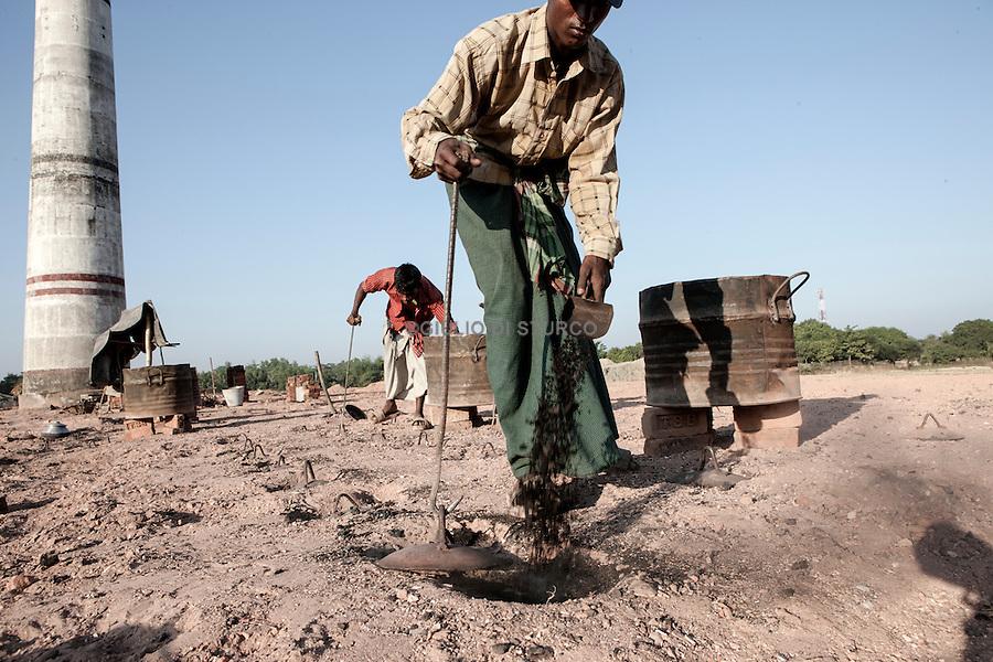 Rohingya migrants carry bricks past a smokestack in a Southern Bangladesh brick factory.