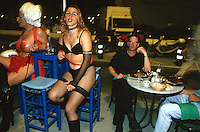 Spain. Ibiza in the Balearic islands. Ibiza. Night life. Two sexy young women, both transsexuals, sit at a café. Two men eat their supper on a plastic table. Transsexualism is a condition in which an individual identifies with a physical sex that is different from their biological one. © 1999 Didier Ruef
