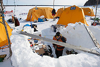 The volunteer crew at the Eagle Island checkpoint sleep in the Arctic Oven tents and cook in their ice cave kitchen during Iditarod 2009