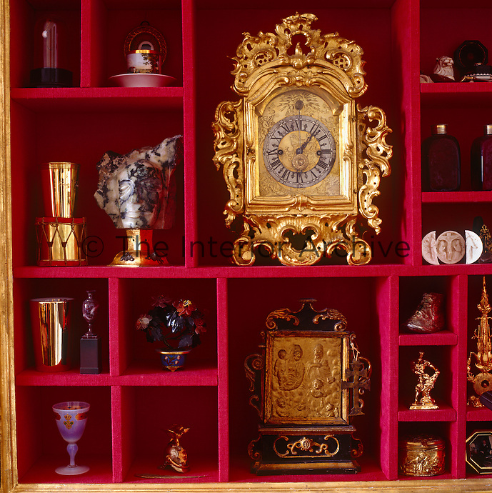 A custom-made cabinet is lined in scarlet creating a stunning backdrop for an antique ormolu clock and collection of bibelots