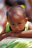 Young boy with green banana leaf, green shirt at a festival, Marquesas Islands, French Polynesia