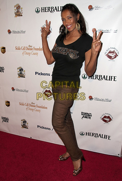 KATHLEEN BRADY.K.I.S. Foundation celebrates the 100th discovery year of Sickle Cell Disease with their Annual Bowling Challenge held at PINZ Entertainment  Center, Studio City, CA, USA..September 17th, 2010.full length black t-shirt brown trousers hands v peace sign.CAP/ADM/DT.©Daniel Tanner/AdMedia/Capital Pictures.