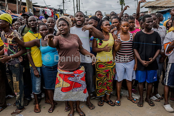 MONROVIA, LIBERIA - AUGUST 23, 2014:   Residents wait for relatives to bring them food from outside of the quarantined area, during the fourth day of the government's Ebola quarantine on the West Point neighbourhood on August 23, 2014 in Monrovia, Liberia.  Liberia's government announced Friday night that it would lift an Ebola quarantine on a large slum here in the capital, 10 days after attempts to cordon off the neighborhood from the rest of the city sparked deadly clashes and fueled doubts about President Ellen Johnson Sirleaf's ability to handle the outbreak.<br /> photo by Daniel Berehulak