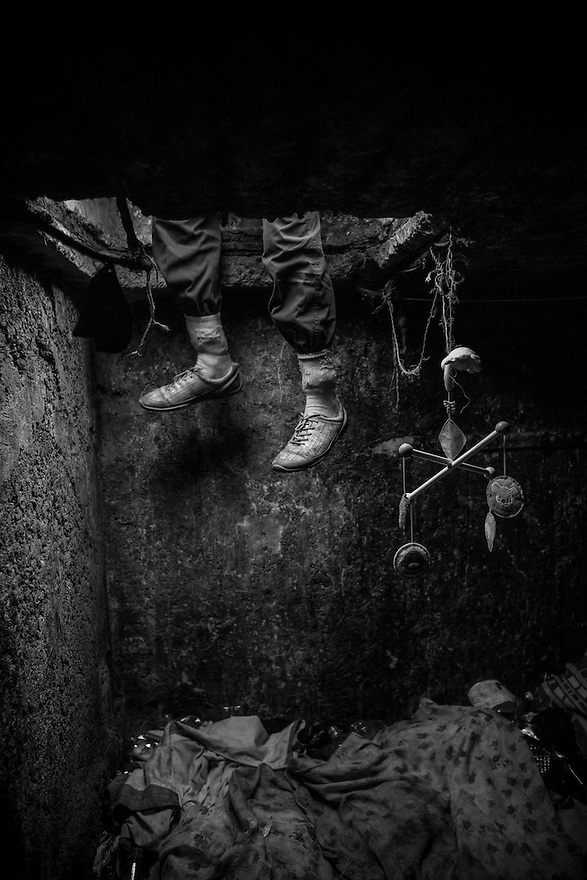 Remus, 26, enters his home underground through a manhole which he keeps covered with plastic in case of rain. A child's mobile hangs from the ceiling for decoration.