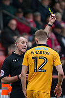 Referee Graham Salisbury shows a yellow card to Scott Wharton of Cambridge United during the Sky Bet League 2 match between Cheltenham Town and Cambridge United at the LCI Stadium, Cheltenham, England on 18 March 2017. Photo by Mark  Hawkins / PRiME Media Images.