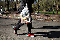 A Runner holds a plastic bag with his personal belongings due to security reasons after the City Parks Foundation Run for the Parks in central Park New York, April 21, 2013. by Kena Betancur / VIEWpress
