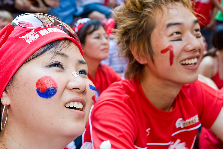 "South Korea fans gather by the hundreds to watch their team play against France on June 18, 2006 on a giant outdoor television in a section of New York City known as ""Korea Way"".<br /> <br /> The World Cup, held every four years in different locales, is the world's pre-eminent sports tournament in the world's most popular sport, soccer (or football, as most of the world calls it).  Qualification for the World Cup is open to any country with a national team accredited by FIFA, world soccer's governing body. The first World Cup, organized by FIFA in response to the popularity of the first Olympic Games' soccer tournaments, was held in 1930 in Uruguay and was participated in by 13 nations.    <br /> <br /> As of 2010 there are 208 such teams.  The final field of the World Cup is narrowed down to 32 national teams in the three years preceding the tournament, with each region of the world allotted a specific number of spots.  <br /> <br /> The World Cup is the most widely regularly watched event in the world, with soccer teams being a source of national pride.  In most nations, the whole country is at a standstill when their team is playing in the tournament, everyone's eyes glued to their televisions or their ears to the radio, to see if their team will prevail.  While the United States in general is a conspicuous exception to the grip of World Cup fever there is one city that is a rather large exception to that rule.  In New York City, the most diverse city in a nation of immigrants, the melting pot that is America is on full display as fans of all nations gather in all possible venues to watch their teams and celebrate where they have come from."