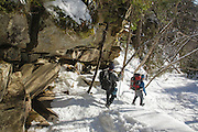 Two hikers descending the Falling Waters Trail in the White Mountains of New Hampshire USA during the winter months