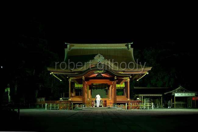 """A pilgrim bows in prayer at the """"maiden"""" inside the grounds of Tsurugaoka Hachimangu Shrine in Kamakura, Japan on  14 Sept. 2012.  Sept 14 marks the first day of the 3-day Reitaisai festival, which starts early in the morning when shrine priests and officials perform a purification ritual in the sea during a rite known as hamaorisai. Photographer: Robert Gilhooly"""