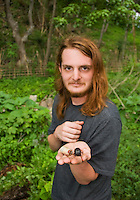 Biology student Scott Heacox holds a rhinoceros beetle and larva, Dynastinae, on Atauro Island, Timor-Leste (East Timor)