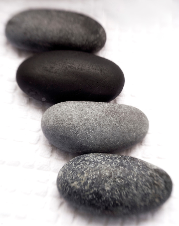 Black Massage Stones on white Towel