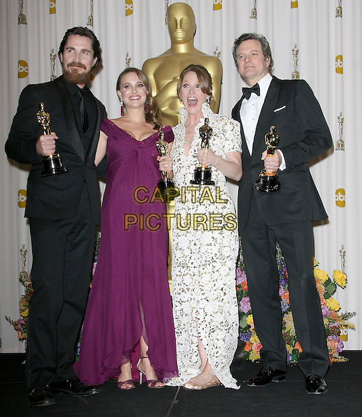 CHRISTIAN BALE, NATALIE PORTMAN, MELISSA LEO & COLIN FIRTH .The 83rd Academy Awards held at The Kodak Theatre in Hollywood, California, USA..February 27th, 2011.oscars press room full length winner mouth open funny trophies trophy black suit jacket beard facial hair  pregnant maternity purple long maxi dress cleavage low cut off the shoulders silk satin sandals jimmy choo shoulder pads dress long maxi white lace high collar tuxedo .CAP/RKE/DVS.©DVS/RockinExposures/Capital Pictures.