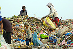 Children and adults working in the municipal dump in Manila, the capital of the Philippines. Children and their parents work day and night in the dump, scavenging for items of value, including plastic, glass and metal, that can be recycled..