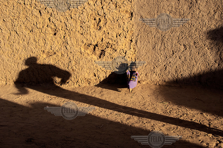 A small child sits against a wall, with a shadow of a person elongated by the sun in the town of Gao, located on the Niger River. /Felix Features